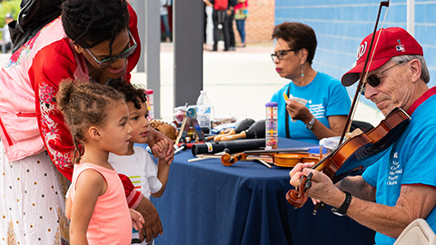 Mom and 2 daugters learning about a violin